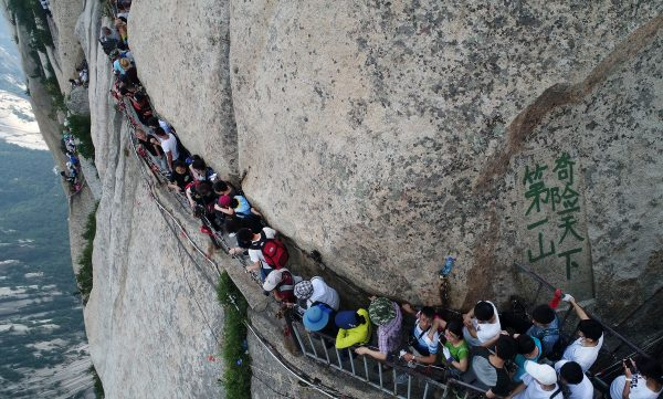 Tourists queue and walk on a plank road built on a cliff